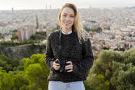 Portrait of smiling young woman with camera at sunrise above the city, Barcelona, Spain - GIOF07707