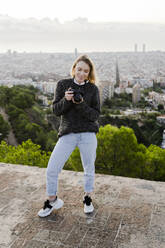 Young woman with camera above the city at sunrise, Barcelona, Spain - GIOF07710