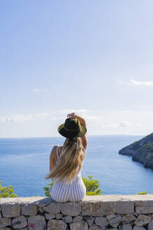 Young woman sitting on a wall and looking at distance, viewpoint in Ibiza - AFVF04226