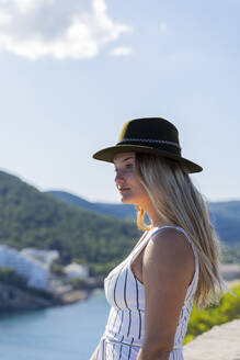 Young woman sitting on a wall and looking at distance, viewpoint in Ibiza - AFVF04229