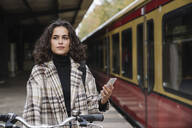 Woman with bicycle and cell phone on an underground station platform, Berlin, Germany - AHSF01198