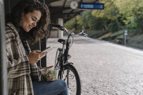 Smiling woman with bicycle having lunch and using smartphone on station platform, Berlin, Germany - AHSF01204
