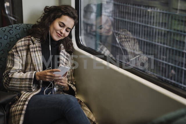 Young woman with earphones using smartphone on a subway - AHSF01219 - Hernandez and Sorokina/Westend61