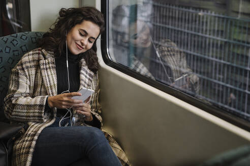 Young woman with earphones using smartphone on a subway - AHSF01219