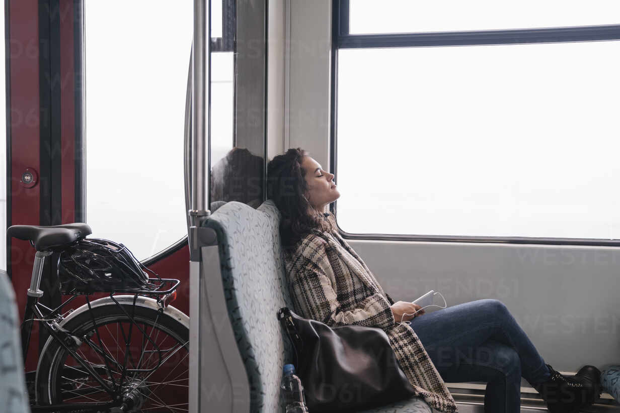 Young woman with closed eyes relaxing on a subway - AHSF01222 - Hernandez and Sorokina/Westend61