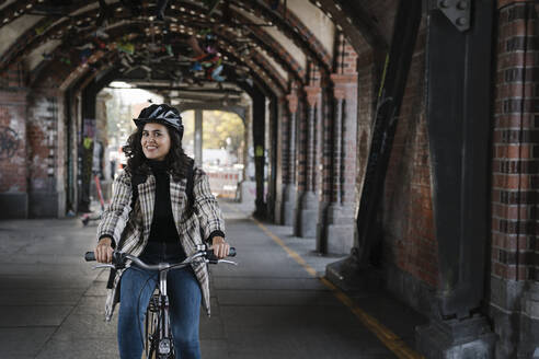 Portrait of smiling woman riding bicycle in the city, Berlin, Germany - AHSF01225