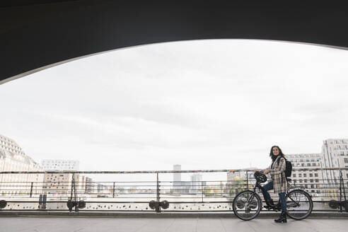Woman with a bicycle standing on a bridge in the city, Berlin, Germany - AHSF01228