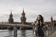 Woman with bicycle and smartphone in the city at Oberbaum Bridge, Berlin, Germany - AHSF01234