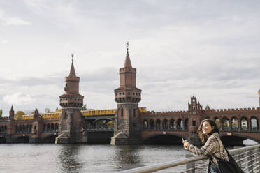 Smiling woman with smartphone in the city at Oberbaum Bridge, Berlin, Germany - AHSF01237