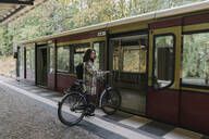 Woman with bicycle entering an underground train, Berlin, Germany - AHSF01240