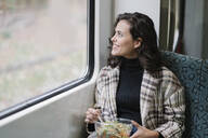 Smiling young woman having lunch on a subway looking out of window - AHSF01246