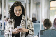 Young woman using smartphone on a subway - AHSF01249