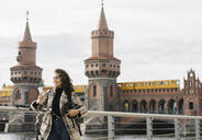 Smiling woman with bicycle using smartphone in the city at Oberbaum Bridge, Berlin, Germany - AHSF01255