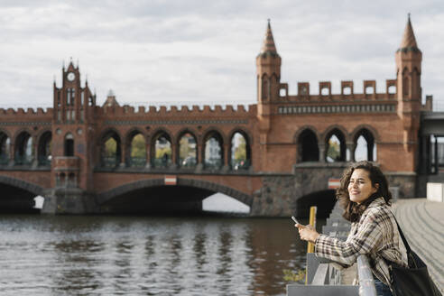 Woman with smartphone in the city at Oberbaum Bridge, Berlin, Germany - AHSF01258