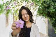 Portrait of young woman with pink flower - AFVF04234