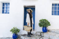 Young woman wearing sun hat and cardigan in front of a blue door - AFVF04243