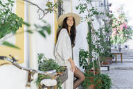 Young woman wearing sun hat and cardigan leaning on a wall - AFVF04246