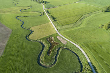 Germany, Bavaria, Aerial view of green countryside fields and meandering Wornitz river - RUEF02372