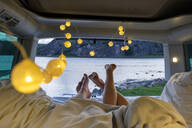 Feet of teenage couple, lying in a camper at the sea - LBF02789