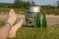 Bare feet of young man in front of camping cooker and empty beer bottles - LBF02792