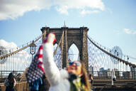 Woman standing on Brooklyn Bridge holding the American flag, New York, United States - OCMF00897