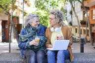 Senior mother with her adult daughter using laptop and drinking juices in the city - RTBF01381