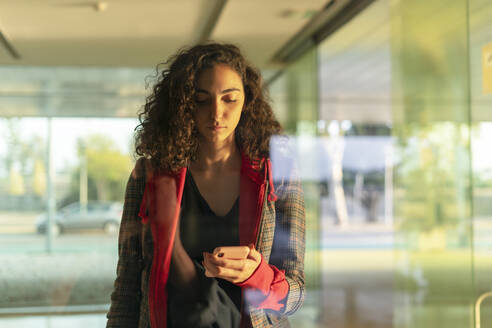 Portrait of young woman behind glass pane looking at cell phone - ERRF02033