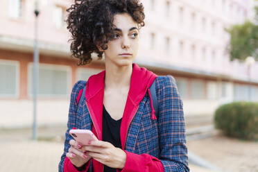 Portrait of young woman with mobile phone looking at distance - ERRF02039