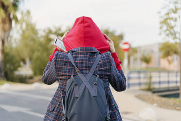 Back view of young woman with backpack and mobile phone putting on hood - ERRF02042