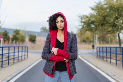 Portrait of young woman wearing hooded jacket standing on the street - ERRF02045