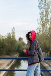 Portrait of young woman with backpack and mobile phone standing on a bridge - ERRF02051