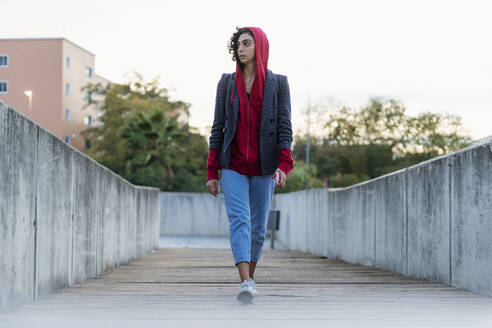 Portrait of young woman walking on bridge looking at distance - ERRF02060