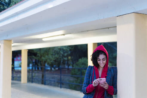 Portrait of happy young woman using mobile phone in the evening - ERRF02063