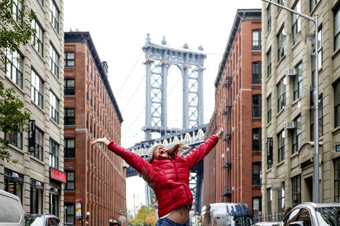 USA, New York, New York City, Young woman jumping against Manhattan Bridge - OCMF00906