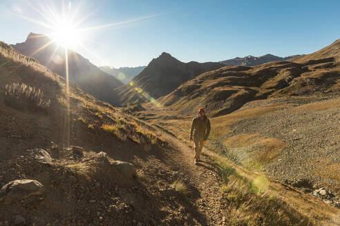 Hiker walking on dirt road against blue sky - CAVF69223