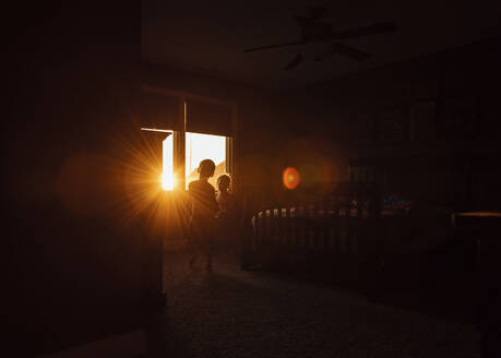 Back lit boys playing in bedroom at home - CAVF69232