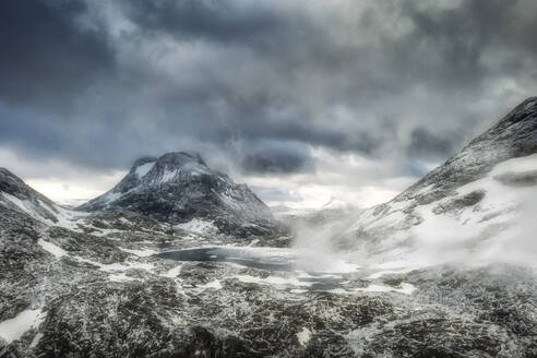 Storm clouds over Olaskarsvatnet lake at feet of the snowcapped Olaskarstind mountain, Venjesdalen valley, Andalsnes, Norway, Scandinavia, Europe - RHPLF12846