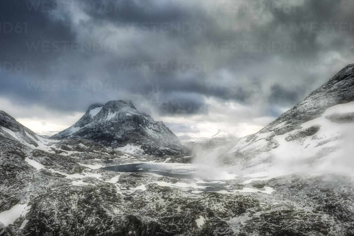 Storm clouds over Olaskarsvatnet lake at feet of the snowcapped Olaskarstind mountain, Venjesdalen valley, Andalsnes, Norway, Scandinavia, Europe - RHPLF12846 - RHPL/Westend61