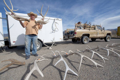 Man holding antlers for sale in Taos, New Mexico, United States of America, North America - RHPLF12960