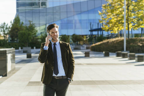 Businessman on the phone in urban business district, Madrid, Spain - KIJF02734