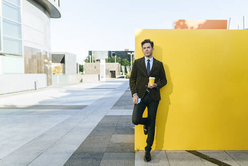Businessman with takeaway coffee and phone next to yellow wall in urban business district, Madrid, Spain - KIJF02746