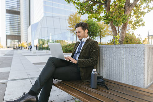 Businessman sitting on bench in the city using laptop, Madrid, Spain - KIJF02755