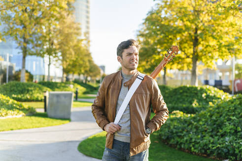 Man in an urban park with guitar, Madrid, Spain - KIJF02767