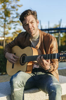 Portrait of man playing guitar outdoors - KIJF02770