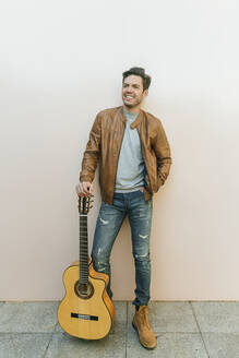 Smiling man with guitar in front of a wall - KIJF02773