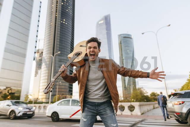 Portrait of screaming man with guitar in the city, Madrid, Spain - KIJF02794 - Kiko Jimenez/Westend61
