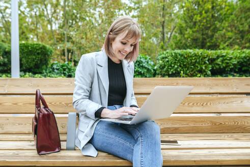 Smiling woman sitting on park bench using laptop - KIJF02797