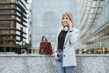 Smiling woman on the phone in the city - KIJF02800