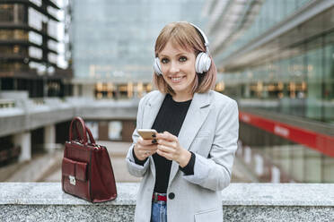 Smiling woman ith smartphone and headphones in the city - KIJF02803