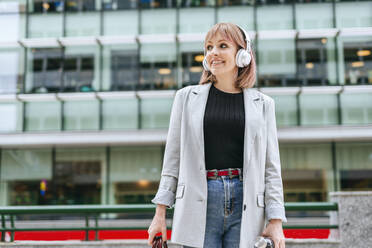 Woman with headphones in the city on the go - KIJF02809